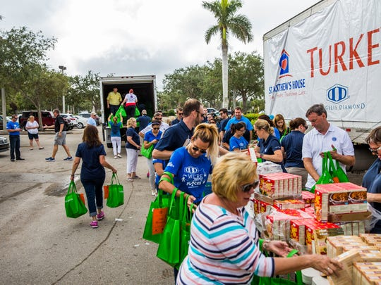Thanksgiving meals are packed in the parking lot next to St. Matthews House in Naples on Friday, Nov. 10, 2017. A thousand meals were prepared for next week's distribution.