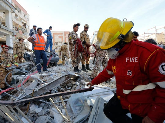 Iranian Red Crescent and rescue workers try to extract the body of a victim from underneath the wreckage of a collapsed building in the city of Pole-Zahab, in Kermanshah Province, Iran, on Nov. 13, 2017.