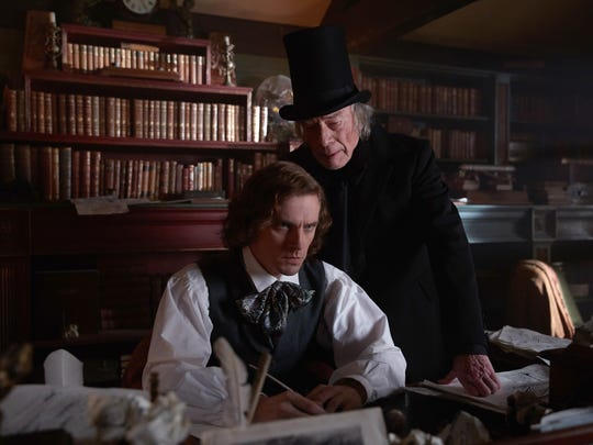"Charles Dickens (Dan Stevens, left) wrestles with a Christmas narrative, with the help of his creation, Ebenezer Scrooge (Christopher Plummer) in ""The Man Who Invented Christmas."""