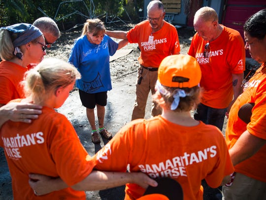 Lori Malone is joined in prayer by volunteers from Samaritan's Purse humanitarian aid outside of her damaged home in Bonita Springs on Sept. 26, 2017.