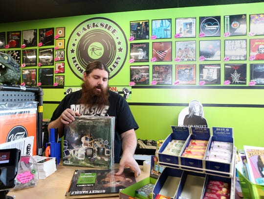 Darkside Records co-owner Justin Johnson sorting records at Darkside Records in the Town of Poughkeepsie.
