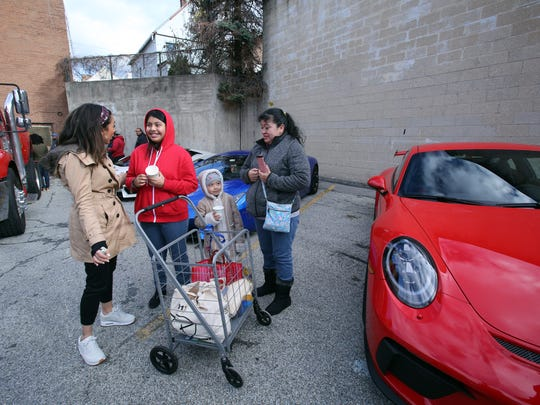 Volunteer Yagmur Akyildiz, left, chats Sunday with sisters Katherine, 12, and Wendy Coatl, 6, and their mother, Guillermina Arellano of Yonkers, during the Precision Concierge New York turkey delivery/exotic car rally at Catholic Charities Community Services in Yonkers.