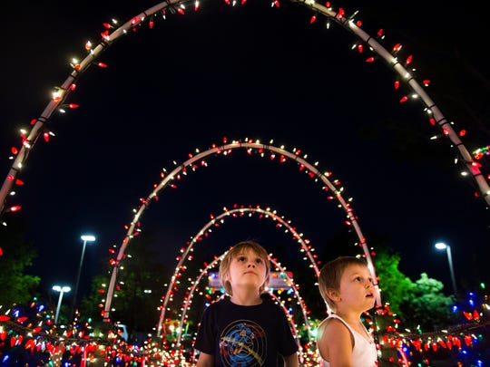 Ridley Cogan, 6, and Seamus Cogan, 4, Philip Baum's sons, look up at the lights on their Naples area home on Tuesday, Nov. 7, 2017. Baum's family helps with the decorations in the months leading up to Thanksgiving.