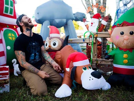 Philip Baum throws his head back in laughter as he stakes down an inflatable Christmas puppy in the Santa's pet store section of his Naples area yard on Sunday, Nov. 19, 2017. Baum groups decorations together to fit themes and provide photo opportunities for visitors.