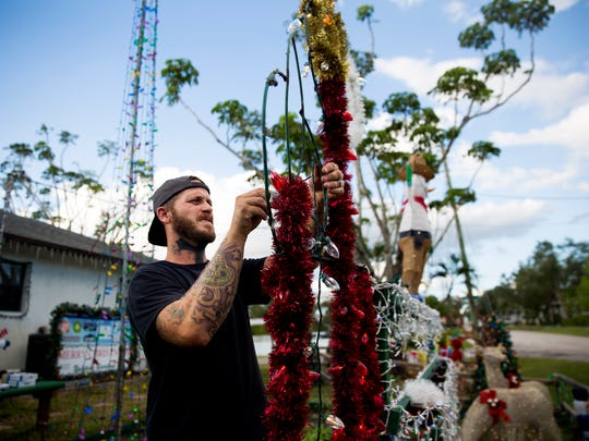 Phillip Baum wraps a candelabra decoration with new lights on Tuesday, Nov. 7, 2017, at his Naples area home. Baum often goes searching for old holiday decorations at thrift stores and estate sales and refurbishes them for his display.