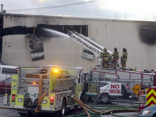 Firefighters battle a fire after an explosion Monday at the Verla International plant, a manufacturer of cosmetics in New Windsor.