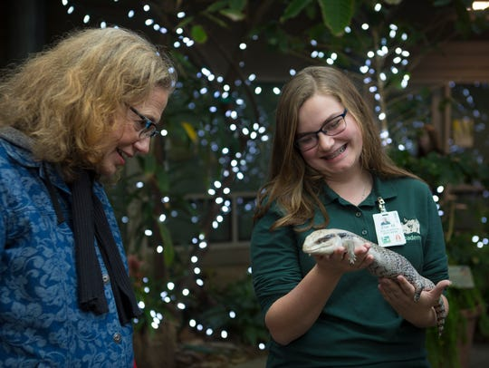 Junior Zoe Miller holds Marvin, a blue-tongued skink, as she answers questions from zoo patrons who walk by. She is attending the Cincinnati Zoo Academy, a Cincinnati Public Schools program that emphasizes science, plant, animal and conservation studies and is housed at the zoo.