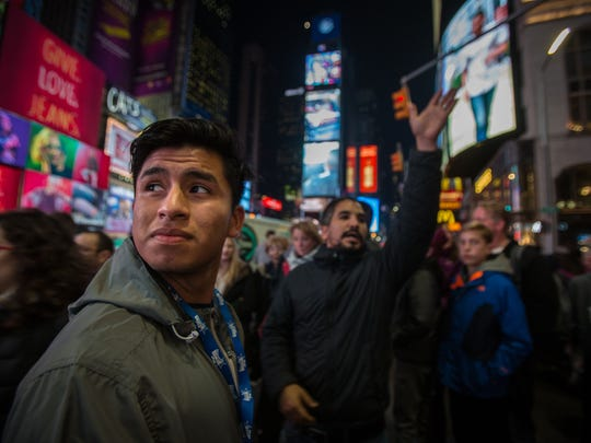 Naples High School student Luis Nicacio looks up at the billboards in Times Square Tuesday, Nov. 21, 2017. Luis was selected to perform with the All American Marching Band  in Macy's Thanksgiving Day Parade.