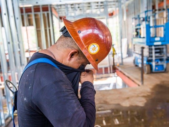 Abednego de la Cruz wipes sweat from his face while working a construction job in Tallahassee on Monday, July 3, 2017. De la Cruz found work after losing an earlier job where he was injured.