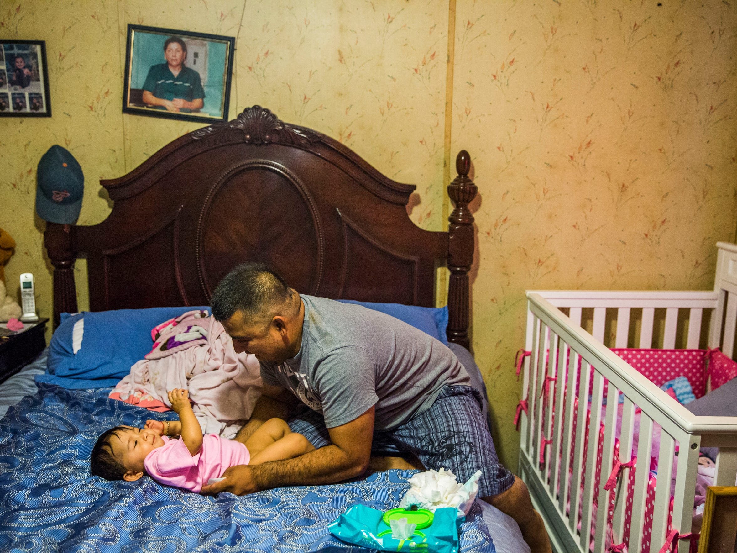 Abednego de la Cruz plays with his daughter Jazlyn, 10 months old, after changing her diaper in their Chattahoochee, Fla., home on Saturday, July 1, 2017. De la Cruz fears he may not be able to raise her. He was one of 163 Florida immigrant workers who were injured, then charged with using a false Social Security number to obtain a job or benefits. Now he faces deportation.