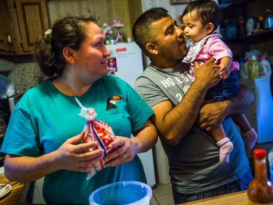 Abednego de la Cruz holds his daughter Jazlyn, 10 months old, while his partner, Blanca Menjivar, prepares dinner in their Chattahoochee, Fla., home on Saturday, July 1, 2017.
