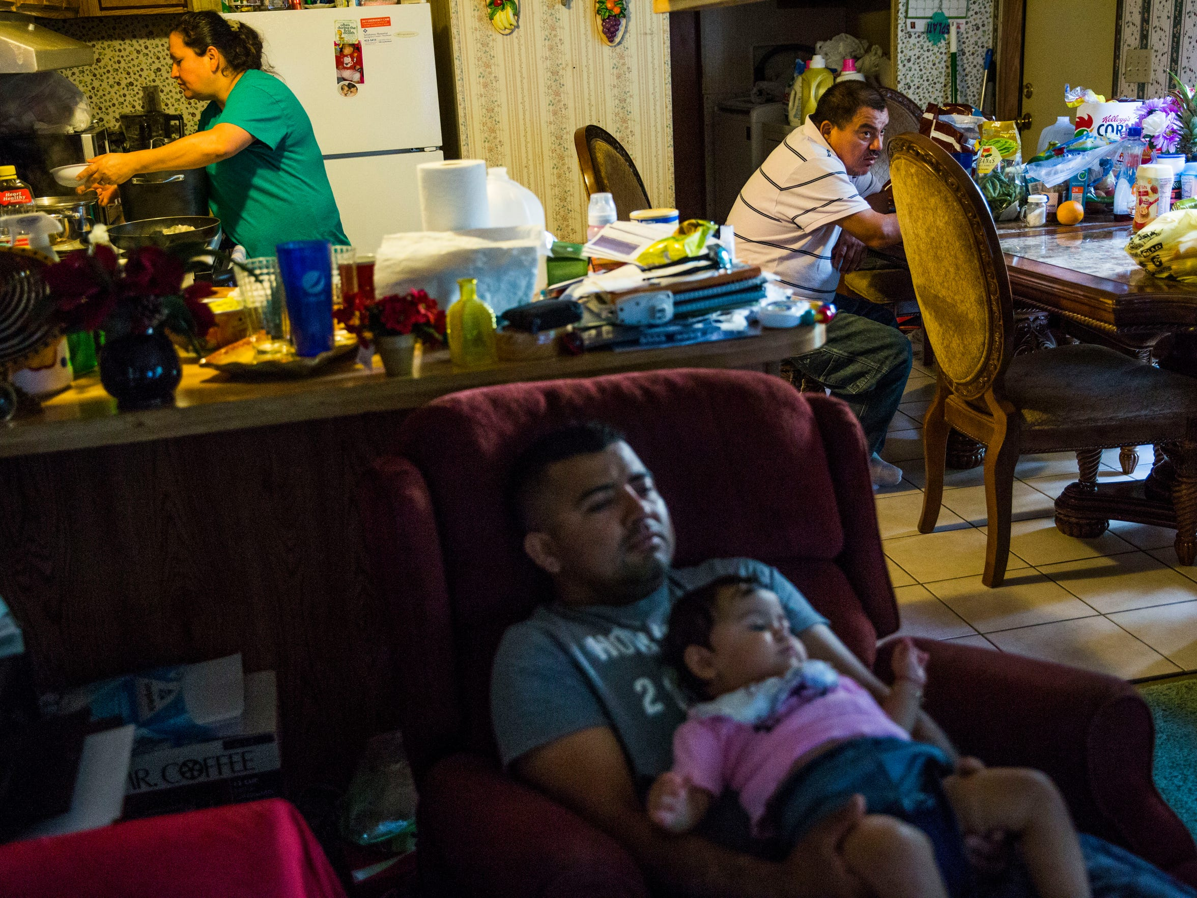 Abednego de la Cruz holds his daughter Jazlyn, 10 months old, while his partner, Blanca Menjivar, prepares dinner in their Chattahoochee, Fla., home on Saturday, July 1, 2017. De la Cruz tries to enjoy time with his family as he faces deportation after a felony arrest for using a false Social Security number to obtain a job. Some Florida companies and insurers report undocumented immigrant workers like de la Cruz after they are injured.