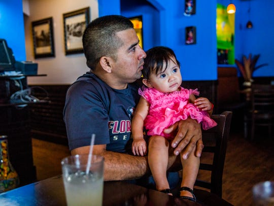 Abednego de la Cruz becomes emotional while holding his daughter Jazlyn, 10 months old, after his immigration hearing in Orlando on Monday, Aug. 7, 2017. He lost his petition for asylum in order to stay in the U.S. and has appealed.
