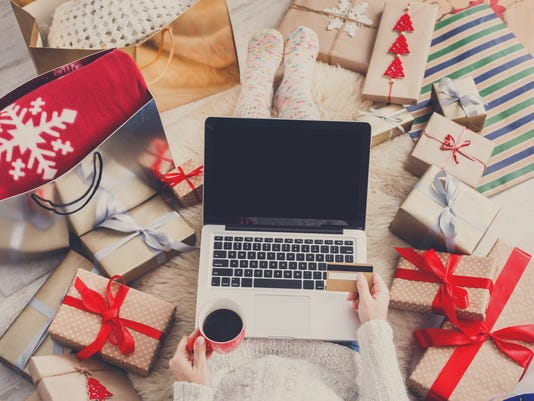 Woman makes christmas shopping online with laptop, above view