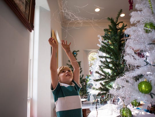 Joshua Robertson, 6, helps decorate Christmas trees to be donated to Rockport families affected by Hurricane Harvey on Wednesday.
