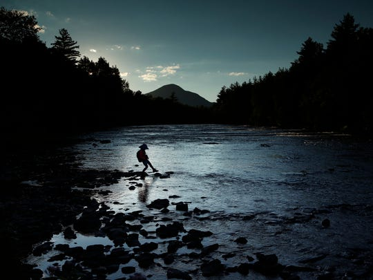 A child explores the Penobscot River's East Branch at the Katahdin Woods and Waters National Monument near Patten, Maine, in 2017.