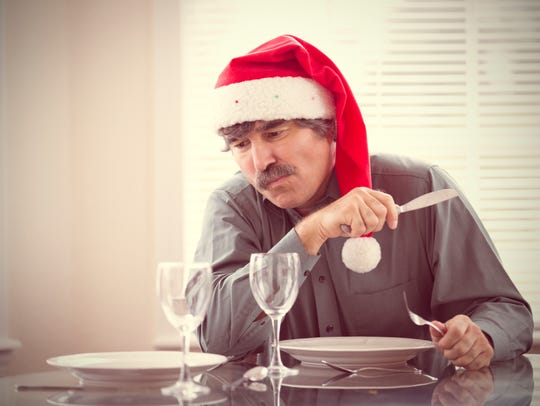 A man with a Santa hat on about to eat a meal.