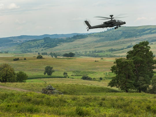 Apaches from the 1st Battalion, 501st Aviation Regiment and Bradley Fighting Vehicles from the 3rd Brigade, 4th Infantry Division out of Fort Carson, Colo., work in tandem during a combined-arms live fire exercise for Getica Saber in Romania.