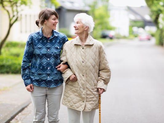 Young caregiver helping senior walking