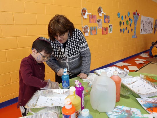 Teacher Rena Kanarek and Meyer Wollner, 7, tidy up the marble painting station.