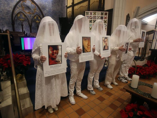 People dressed in veils hold photographs of individuals