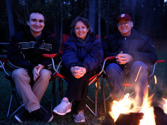 "Daniel (left to right), Gloria and Kevin Allison sit by a fire in their back yard Dec 9. The family has been putting on a Christmas light display they call the ""Allison Christmas Spectacular"" at their house off of Highway 27 North for ten years."