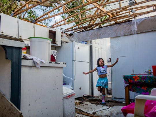 Maria Romero, 6, steps over debris in her home the morning after Hurricane Irma came through Immokalee on Monday, Sept. 11, 2017. The storm ripped off the roof of her family's trailer. The family has nowhere to go.