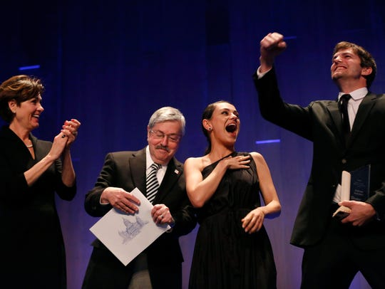 Actress Mila Kunis laughs as Gov. Terry Branstad and