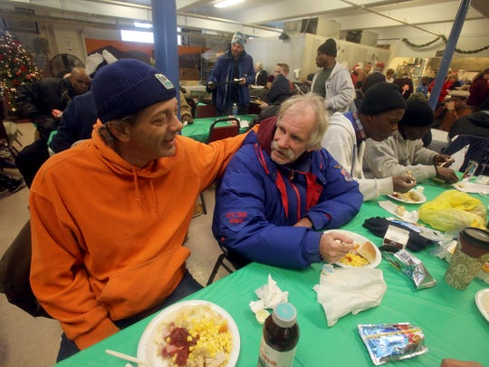 Paul Moschitta, left, and Duane Byble, both of Poughkeepsie, have dinner together during the annual Eileen Hickey Holiday Dinner at the Lunchbox at the Family Partnership Center in Poughkeepsie Dec. 25, 2017.