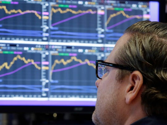 In this Monday, Dec. 4, 2017, file photo, specialist Gregg Maloney works at his post on the floor of the New York Stock Exchange.