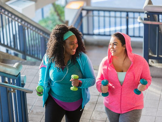 Two young women exercising, powerwalking up stairs