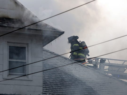 Firefighters work to put out a house fire on Park Avenue