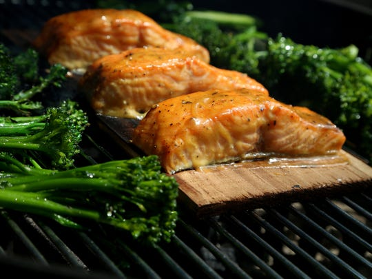 Cedar Plank Dijon Salmon with Broccolini on the grill on Wednesday, August 9, 2017.