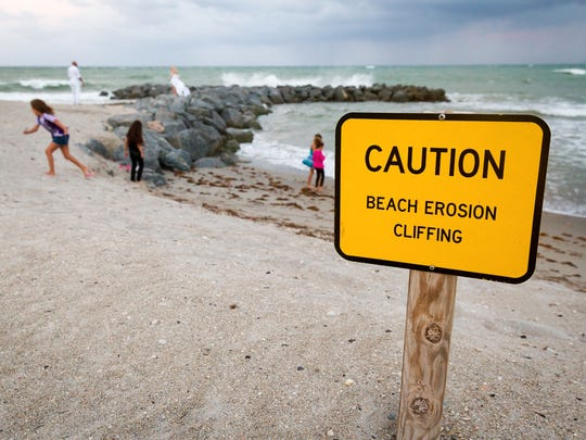 A sign warns beachgoers about erosion at Dr. Von D. Mizell-Eula Johnson State Park (formerly known as John U. Lloyd Beach State Park) in October 2015. The state park is just south of Fort Lauderdale's beach and the Port Everglades inlet in Broward County. The park shoreline has critical erosion problems caused by the inlet's blockage of the natural north-to-south flow of sand along Florida's east coast.