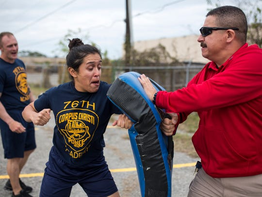 Police cadet Patsy Silva hits a bag after being exposed