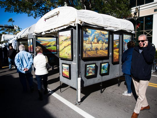 People check out booths at the 22nd annual Naples New Year's Art Show on Saturday, Jan. 6, 2018, on Fifth Avenue South.