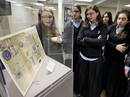"In this Wednesday, Jan. 10, 2018 photo, program Coordinator Miryam Gordon, left, of the Amud Aish Memorial Museum, in Brooklyn, N.Y., leads a tour of the museum's ""Precious Gift: Rescue and Shanghai"" exhibit with a group of students from Brooklyn's Nefesh Academy. The museum focuses on Jewish religious practice and the role of faith during the Holocaust. (AP Photo/Richard Drew)"