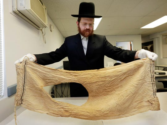 In this Wednesday, Jan. 10, 2018 photo, Dovid Reidel, Director of Research & Archive Division of the Amud Aish Memorial Museum, in Brooklyn, N.Y., holds a talit, or prayer shawl, part of the museum's collection, that belonged to Mendel Landau, in 1944, of Auschwitz, Poland. The museum focuses on Jewish religious practice and the role of faith during the Holocaust. (AP Photo/Richard Drew)
