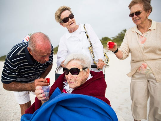 Russ Thomas leans in to wish Solveig Birkeland a happy 102nd birthday as her daughter, Susan Butler and Lorie Thomas raise their glasses for a toast on Friday, January 12, 2018 on Barefoot Beach in Bonita Springs.