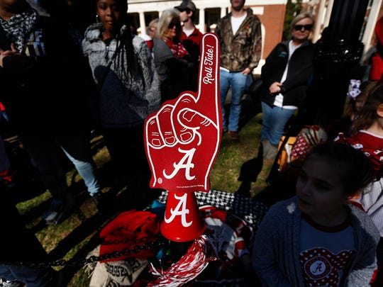 A fan placed a foam finger on a sidewalk gate before the NCAA college football national championship parade, Saturday, Jan. 20, 2018, in Tuscaloosa, Ala. Alabama won the national championship game against Georgia 26-23 in overtime. (AP Photo/Brynn Anderson)