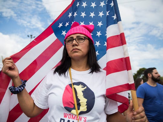 "Vivian Ivalo, 50, who is originally from Argentina and lives in Miami, stands with an American flag during the Women's March Florida at Mana Wynwood in Miami on Jan. 21, 2018. ""I attended this because I feel empowered by the people around me. This is my second march,"" Ivalo said."