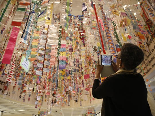 A Capitol visitor admires the artwork of children from across the state, which was strung up by volunteers during the annual Hanging of the Hands in the Capitol rotunda Sunday. The event kicks off this year's Children's Week at the Capitol.