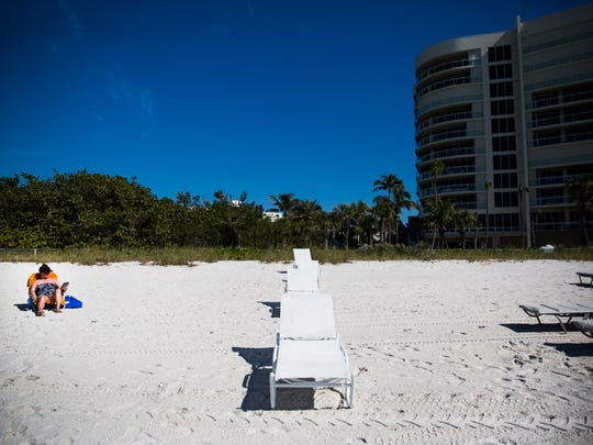 Sue Dempsey sits next to a line of chairs that divide the Moraya Bay Beach Tower private beach from the Bluebill public beach access point on Wednesday, Jan. 24, 2018, in North Naples.