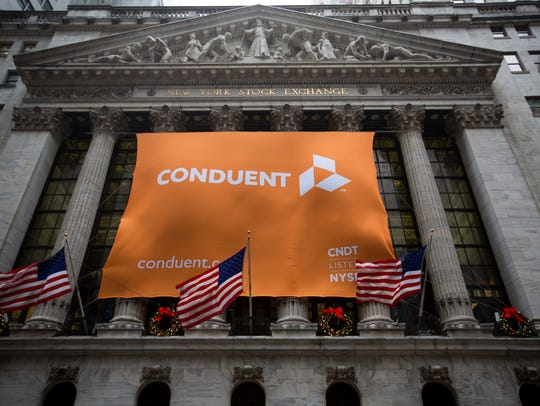 Conduent sign displayed as U.S. flags fly outside the New York Stock Exchange on Jan. 3.