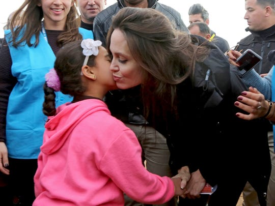 Actress Angelina Jolie kisses a Syrian child during