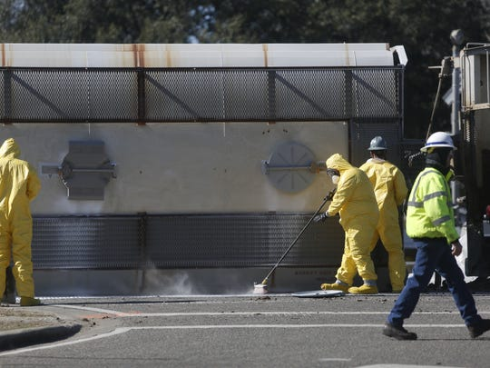 A CSX cleanup team collects adipic acid that leaked from a train car that derailed in downtown Quincy Tuesday morning. The powdery substance posed a very low risk to passersby.