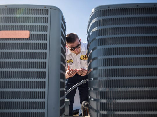 Chandler Evans works on an air conditioning installation in the 2500 block of Airport-Pulling Road on Wednesday, Jan. 31, 2018.