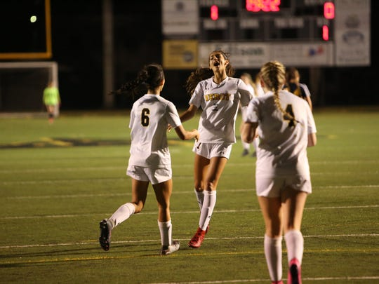 Bishop Verot players Nina Gulati (6) and Lander Peck (4) congratulate Nicole Gulati after scoring a goal against Sarasota Military Academy in a regional quarterfinal on Tuesday. Verot win 8-0.