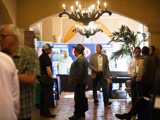 Farmers, agricultural scientists and agricultural company product representatives mingle and talk during a break at the 2018 New Mexico Chile Conference at Hotel Encanto, Tuesday Feb. 6, 2018.