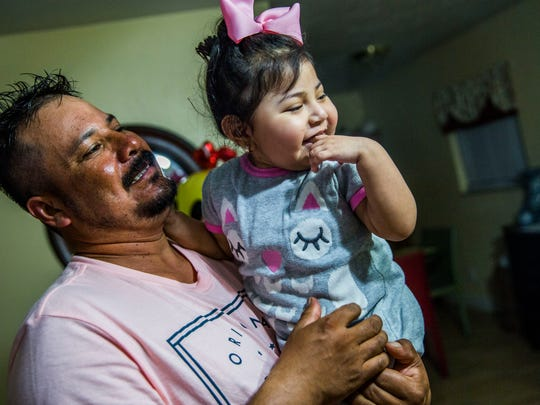 Artemio Hernandez holds his daughter Alicia Hernandez,